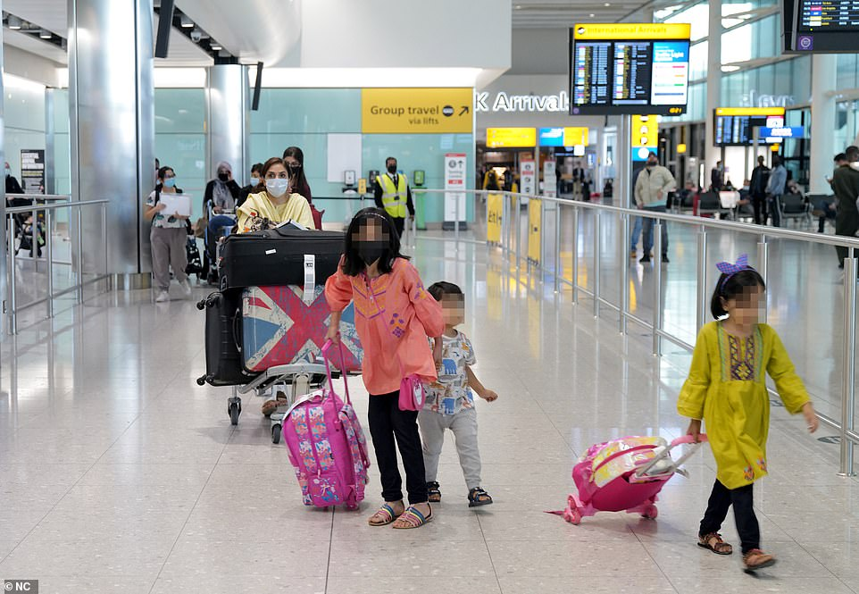 Three children walk in front of a woman at the arrivals hall at London Heathrow Airport's Terminal 2