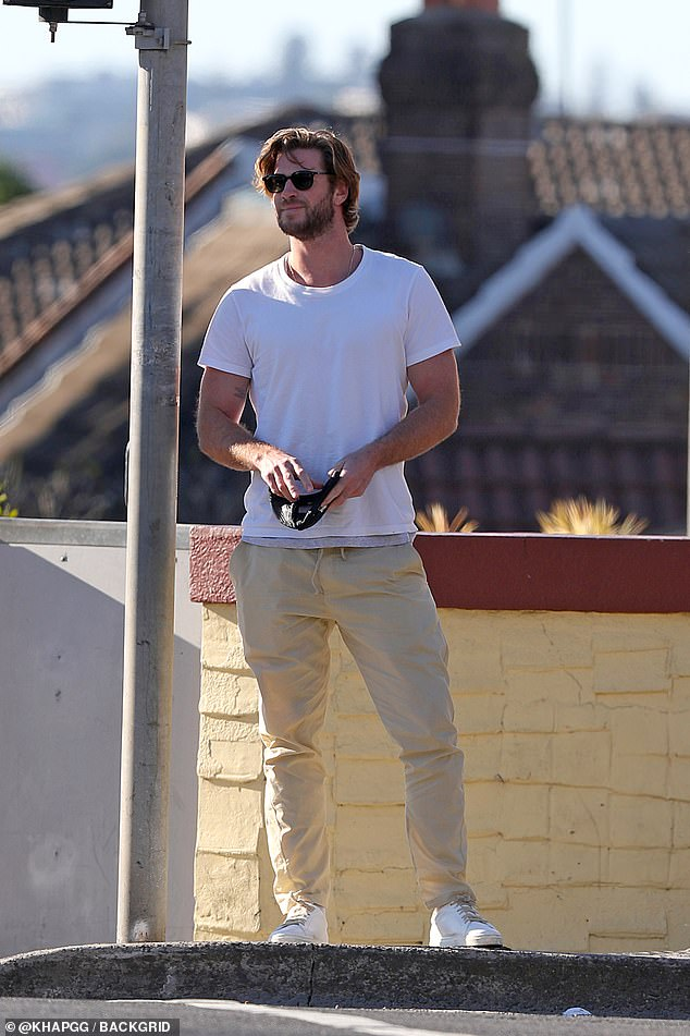 Model good looks: Liam looked suave as he waited to cross the street in Sydney's Bondi after meeting his family for lunch