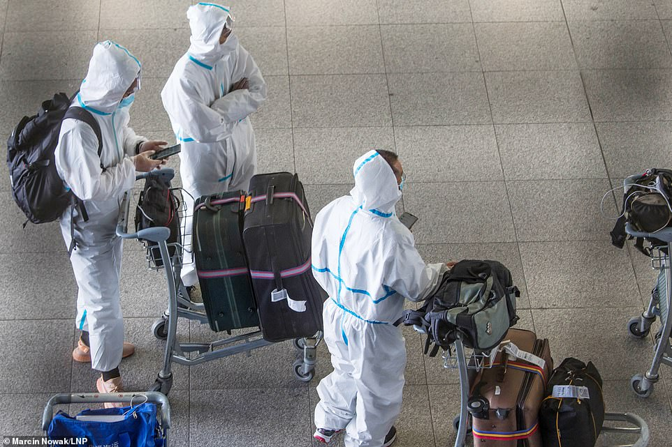 These passengers had taken impressive precautions today - arriving at Heathrow wearing full PPE overalls