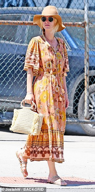 Nicky stepped out in a pair of sandal flats and carried a straw purse with round wood handles