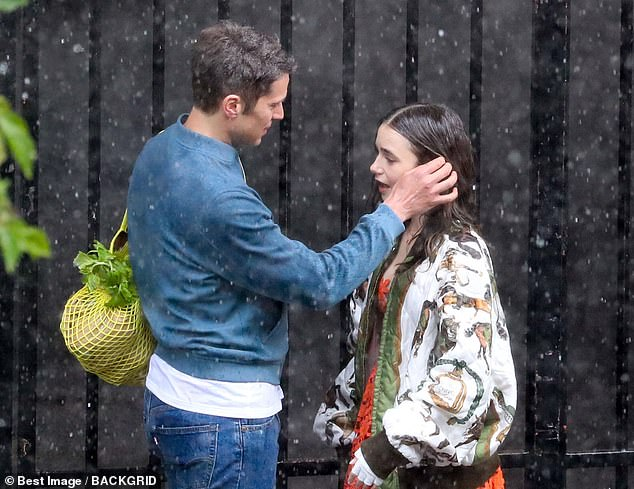 Braving the rain!Lily Collins braved the pouring rain in Paris, France, on Wednesday to shoot cosy scenes with her onscreen love interest Lucas Bravo for Emily In Paris series two