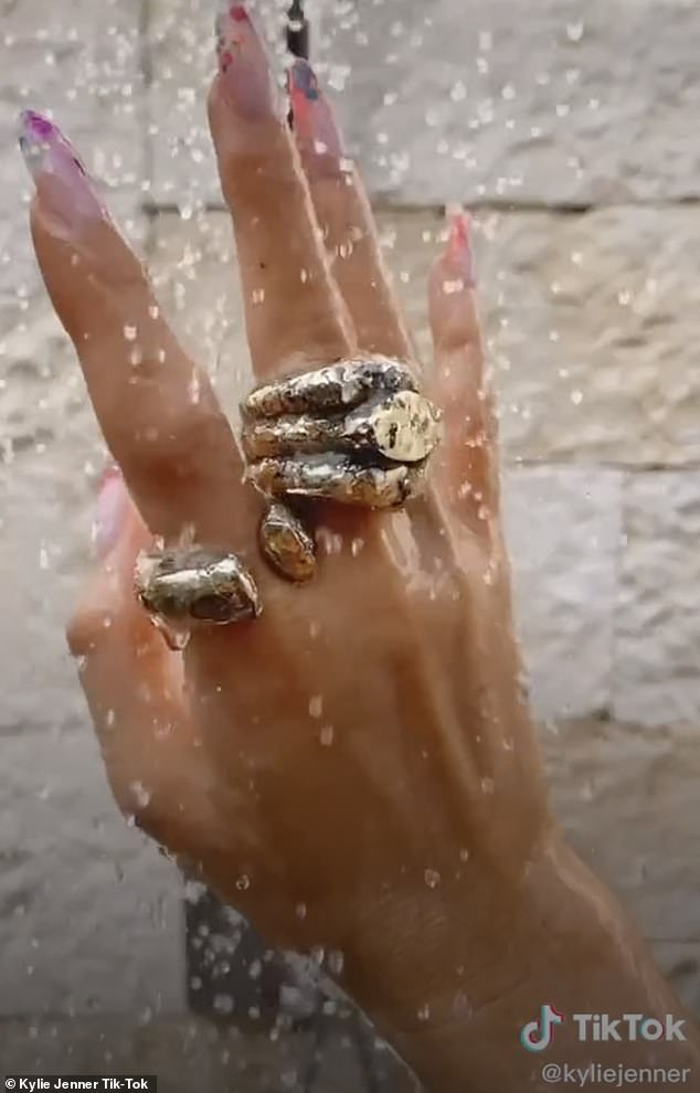 Sizzling:During an evocative part of the video she wore a few elaborate gold rings and curled her fingers while water showered down on them