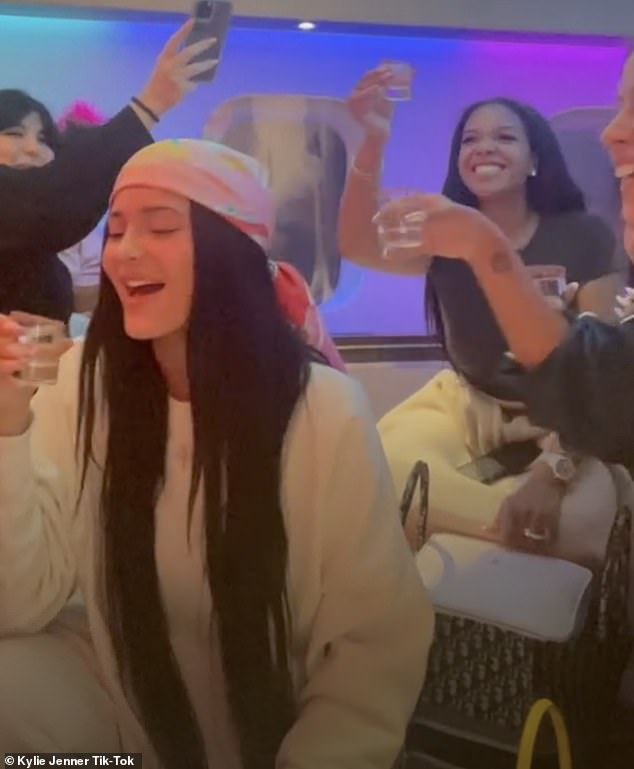 Having a ball:In one brief clip Kylie had a huge smile on her face as she and a group of her friends cheerfully raised drinks for a toast