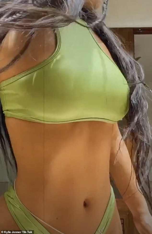 Looking fab:Kylie flaunted her sensational figure, especially her impressively trim midriff, in a lime green bikini for one of her clips