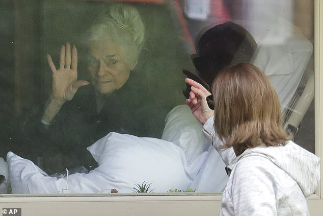 A nursing home resident who tested positive for COVID in the Kirkland, Washington outbreak visits with her daughter through a window