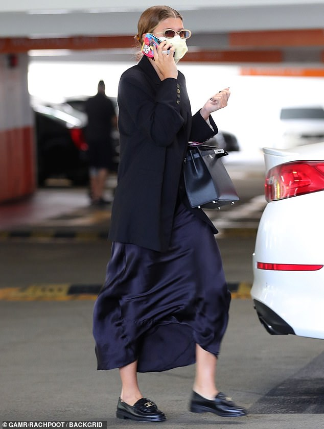 Busy:The model appeared deep in conversation as she headed to her car, holding her iPhone up to her ear as she walked