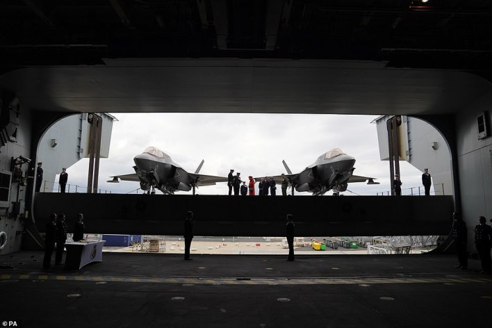 The Queen (above) is seen going on to the flight deck, with a pair of F-35B Lightning II aircraft on either side, during a visit to HMS Queen Elizabeth at HM Naval Base