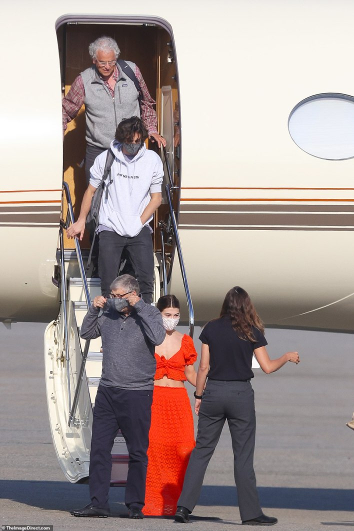 Gates headed down the steps maskless before putting on a matching grey check face mask as he reached the tarmac
