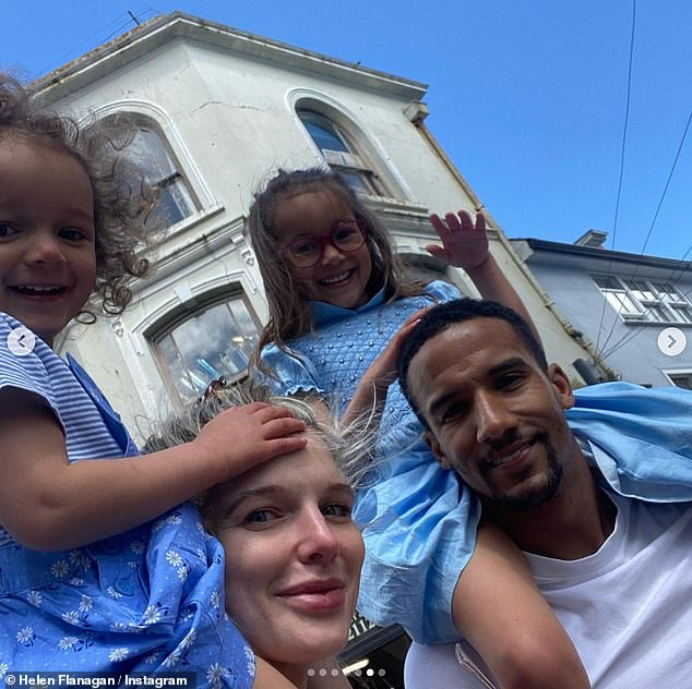 Family fun: In a snap with the whole brood, Helen balanced Delilah on her shoulders, while Scott carried Matilda as they strolled through the streets