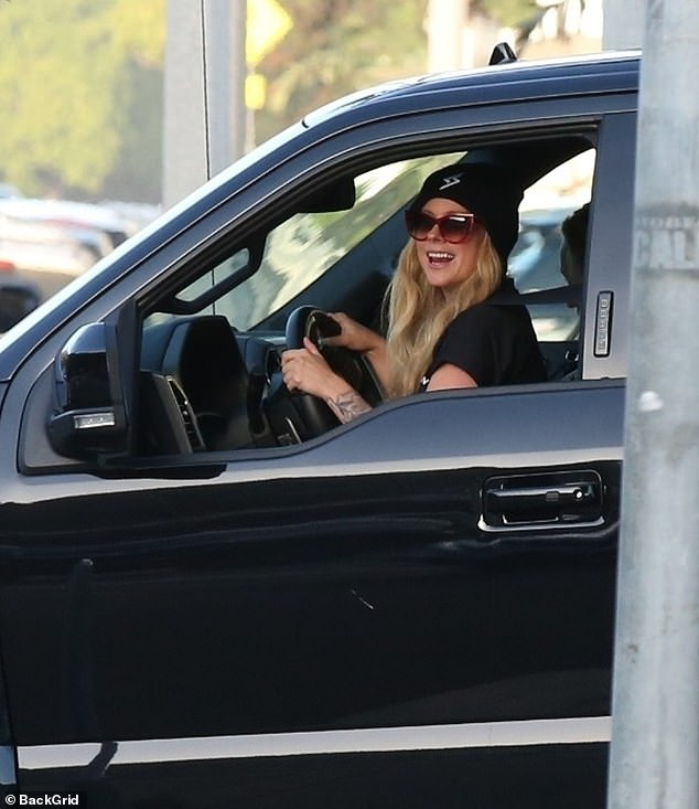 Beaming: The Sk8er Boi singer flashed a big smile as she made her way out of the restaurant