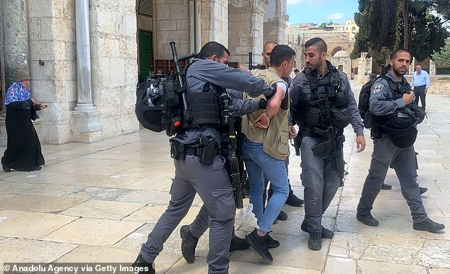 Pictured: Israeli security forces take into custody a Palestinian as Jewish extremists make a raid on Al-Aqsa Compound in East Jerusalem on May 23