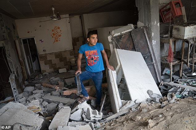 A child stands inside a severely damaged building neighbouring the crater where the home of Ramez al-Masri was destroyed by an air-strike prior to a cease-fire reached after an 11-day war