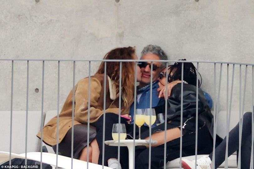 In the middle: Taika draped one arm over Tessa while Rita leaned in to plant a peck on his cheek