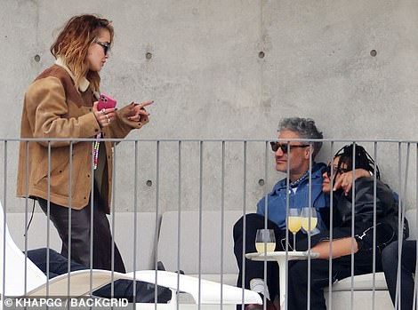 Where've you been? Rita walked over to Taika and Tessa holding onto her pink phone