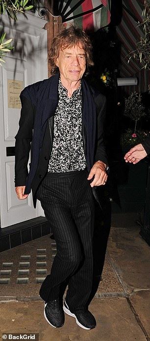 Stylish: Mick looked typically stylish in pinstripe trousers and a black and white shirt that featured a TV static print