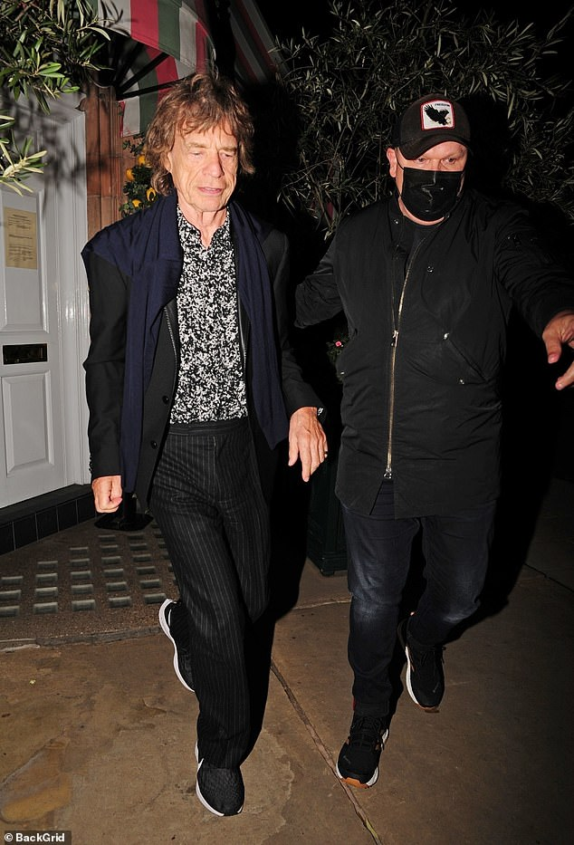 Icon: The iconic musician was escorted to his car by a security member wearing a mask in keeping with pandemic protocol