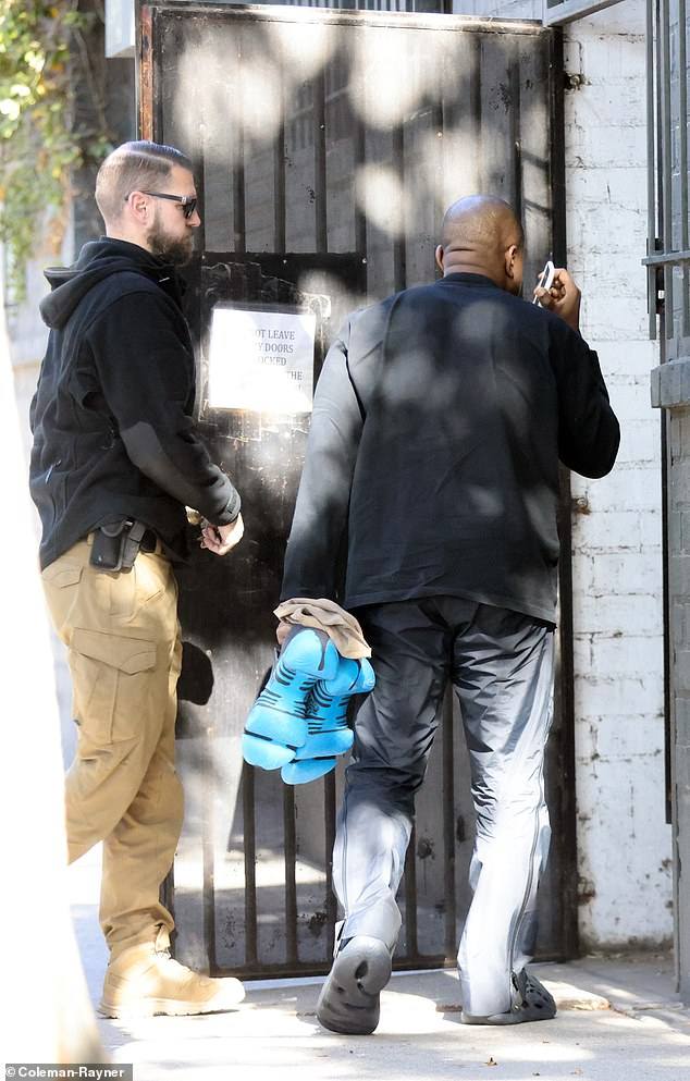 Flanked: The rapper was accompanied by a security guard as he entered a building in LA
