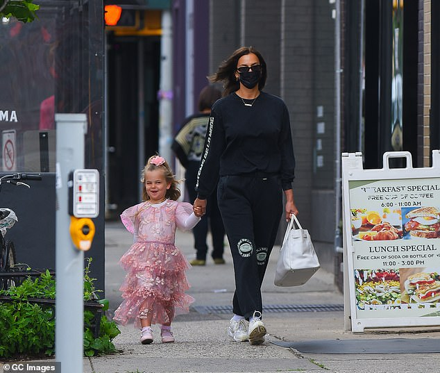 Mom duty: Irina was earlier seen walking with her daughter Lea, who she shares with ex Bradley Cooper