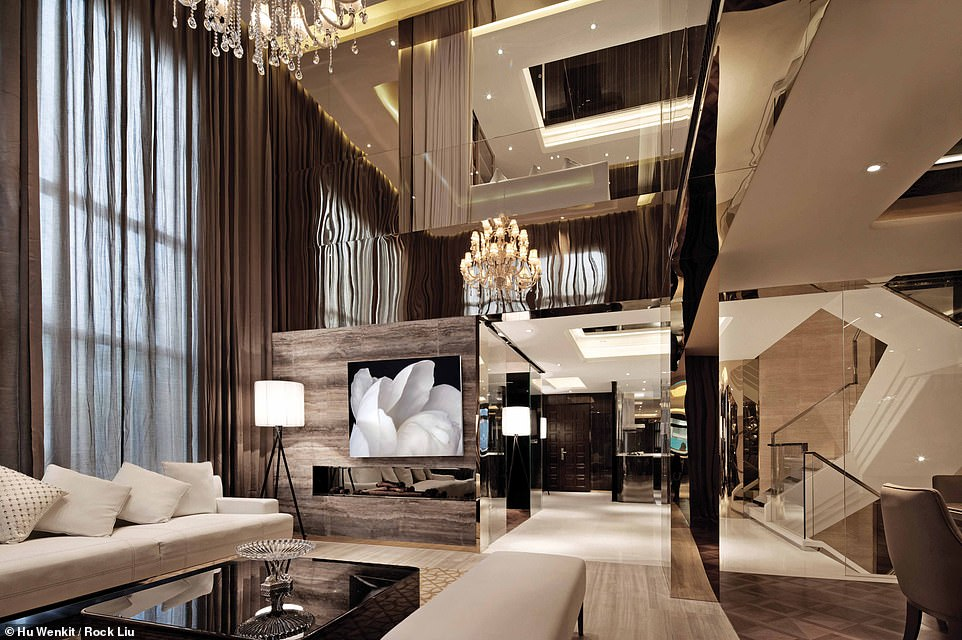 GOLDEN EYE LUXURY HOUSE, JIANGSU, CHINA: This opulent-looking space is the main living area at Golden Eye. It features a soaring ceiling and bronzed walls. 'Entering the volume, one sees simple, espresso-hued curtains running from floor to ceiling,' says Wong. 'Turn around, however, and one sees something quite different. Layered L-shapes create a complex pattern, as does the asymmetric fireplace above which hangs a black-and-white image of a peony, referencing the proportional perfection and evolution of forms in nature'