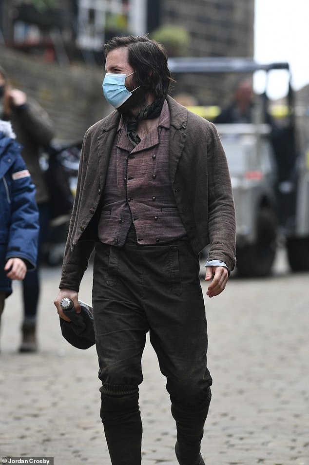 Safety first: An extra was seen wearing a face mask while walking around set, following Covid-19 restrictions amid the global pandemic