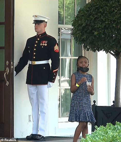 A Marine holds the door open for Gianna Floyd, 6, as she wandered outside the Oval Office doors earing some ice cream