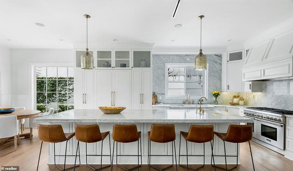 The high-end kitchen includes a marble sink, top-of-the-range stainless steel appliances and a breakfast counter that seats six