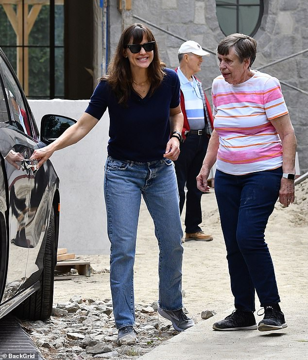 Comfy:She tucked a blue polo top into the waistband of her boot cut jeans and slipped her feet into some of her comfiest sneakers