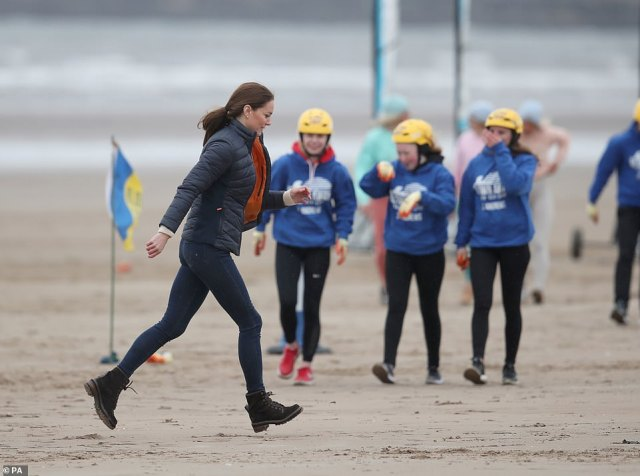 Quick sprint: The Duchess of Cambridge hurried across the rainy beach during the engagement this morning