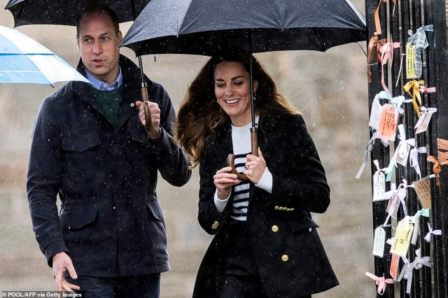 Braving the rain! The couple were in good spirits as they toured the grounds despite the drizzly weather