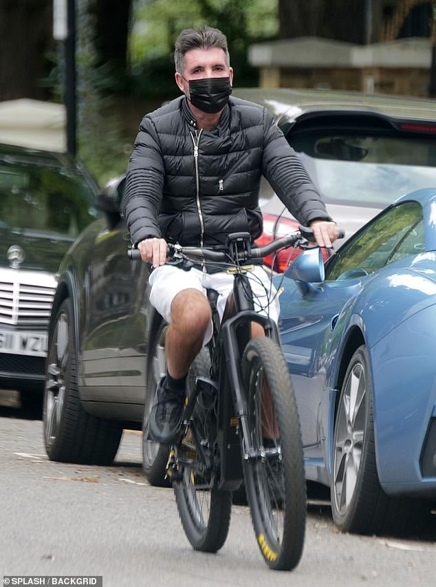 Keeping fit: Simon Cowellwas back on his E-bike as he cycled around West London on Thursday