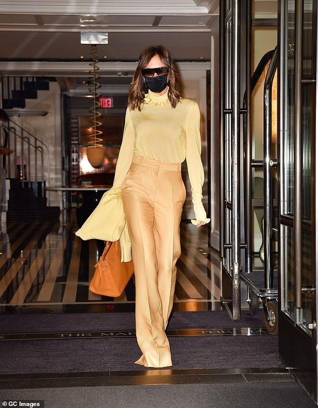 Amazing:Victoria was opting for citrus hues as she stepped out in the ensemble, which boasted alarmingly long trousers which concealed her heels