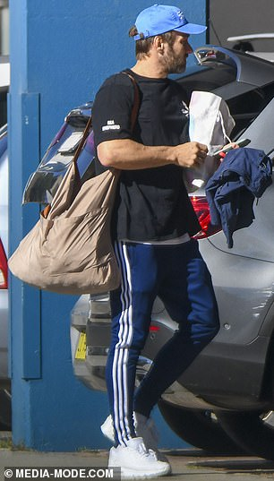 Joel dressed comfortably in blue Adidas sweatpants and a black T-shirt