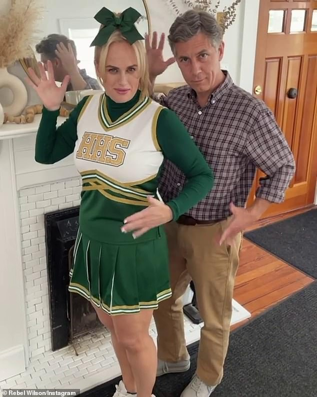 On set fun: Rebel looked slimmer than ever while wearing a cheerleader uniform on the set of high school comedy Senior Year on Wednesday. Pictured with co-star Chris Parnell