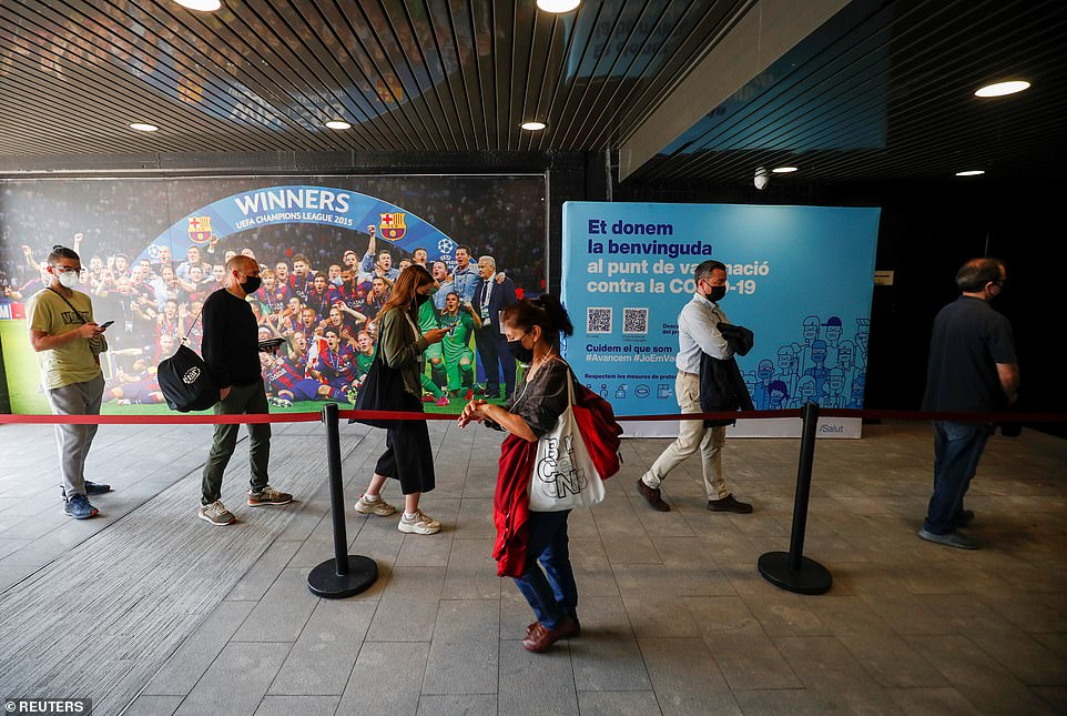 People wait in a line to receive vaccinations in Barcelona today after Spain lifted the travel restriction from the UK