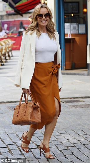 Matching: The blonde beauty teamed the wraparound piece with a structured white blazer but made sure to colour coordinate her shoes and handbag with her skirt