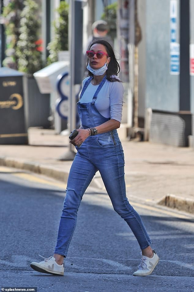 Staying connected: She opted for comfortable white trainers and added a pop of colour with pink rimmed shades as she seen clutching her mobile phone