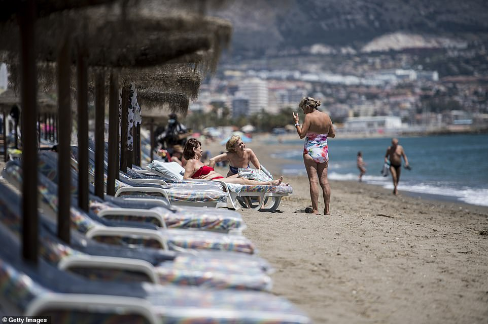 Three women talk to each other while sunbathing on the beach at Fuengirola near Malaga in Spain on Monday