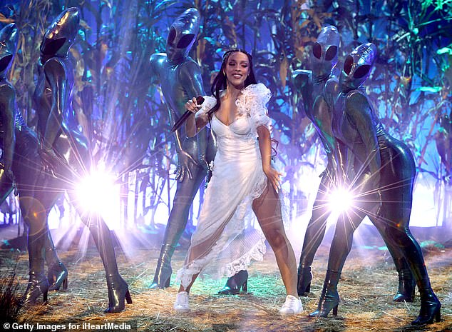 Having fun: The star donned a lacy white dress and trainers for the performance, which saw her joined on stage by dancers clad as aliens