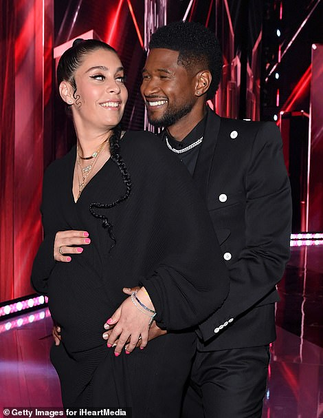 Expecting: Once inside, Usher and his pregnant girlfriend Jenn Goicoechea cozied up for a few snapshots together in front of the iHeartRadio Music Awards stage