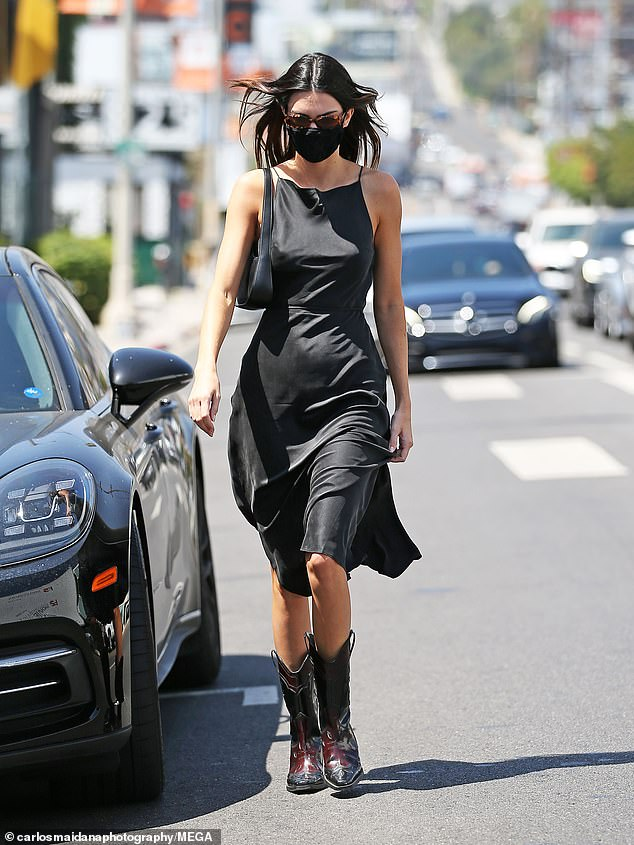 The model had her dark locks down and parted and accessorized with a black purse on the spring day