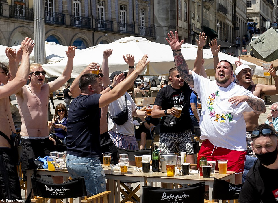 A group of English football fans enjoy their pints in a bar as they chant near the river Douro in Porto, Portugal