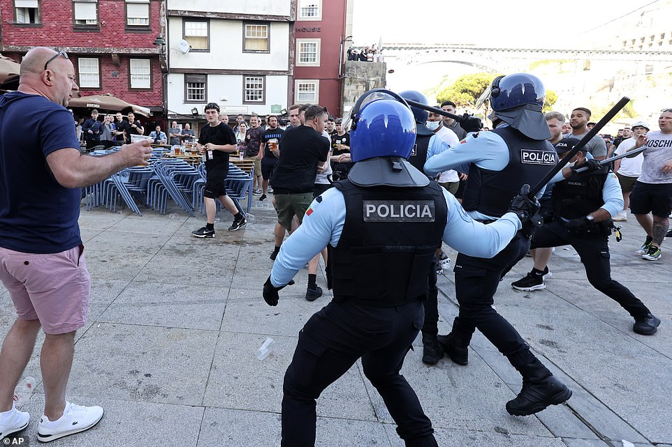 Police moves in to stop a scuffle that started among Manchester City supporters drinking by the Douro river bank in Porto, May 28, 2021. English clubs Manchester City and Chelsea will play the Champions League soccer final in Porto on Saturday