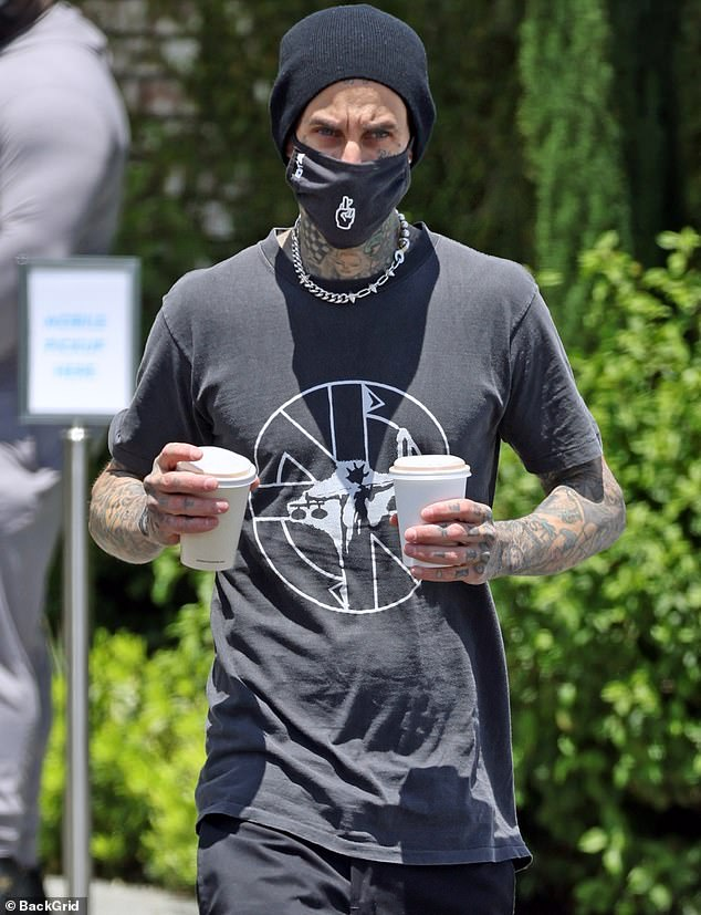 Out and about:Travis Barker modeled a glittering necklace when he was spotted stepping out in sunny Los Angeles this week