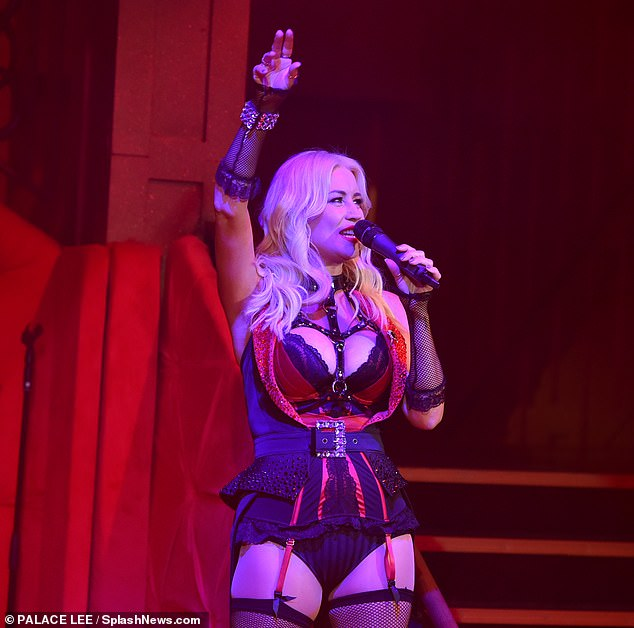 Hot stuff:She belted out songs and entertained the crowds in a busty lace corset and fishnet stockings which were attached together with red suspenders