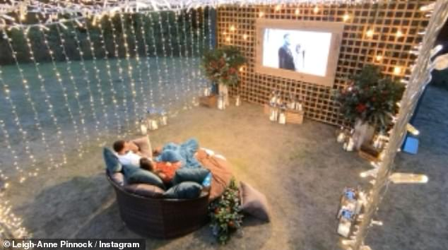 Stunning:In the clip, the happy couple are seen enjoying a movie night in the garden, with the romantic setting adorned with fairy lights and cosy cushions