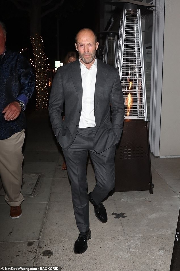 Suave: Jason, 53, looked dapper in a dark grey blazer and matching trousers which he wore with a white shirt