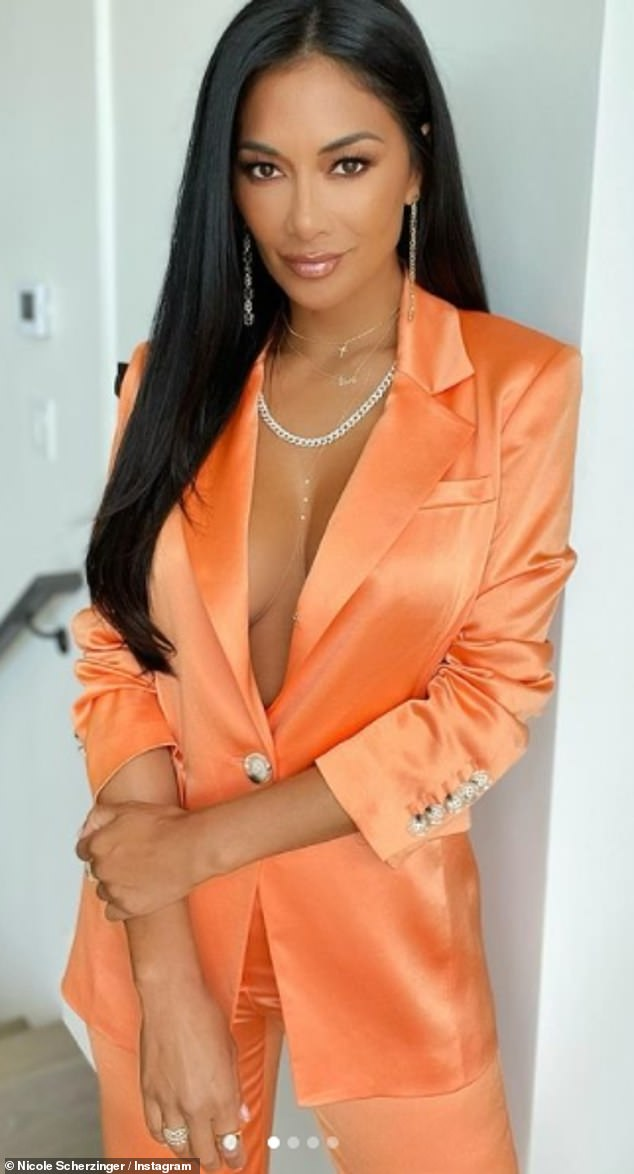 Stunning: Nicole Scherzinger posed up a storm as she flashed cleavage dressed in an orange suit in a series of photos uploaded to her Instagram on Saturday