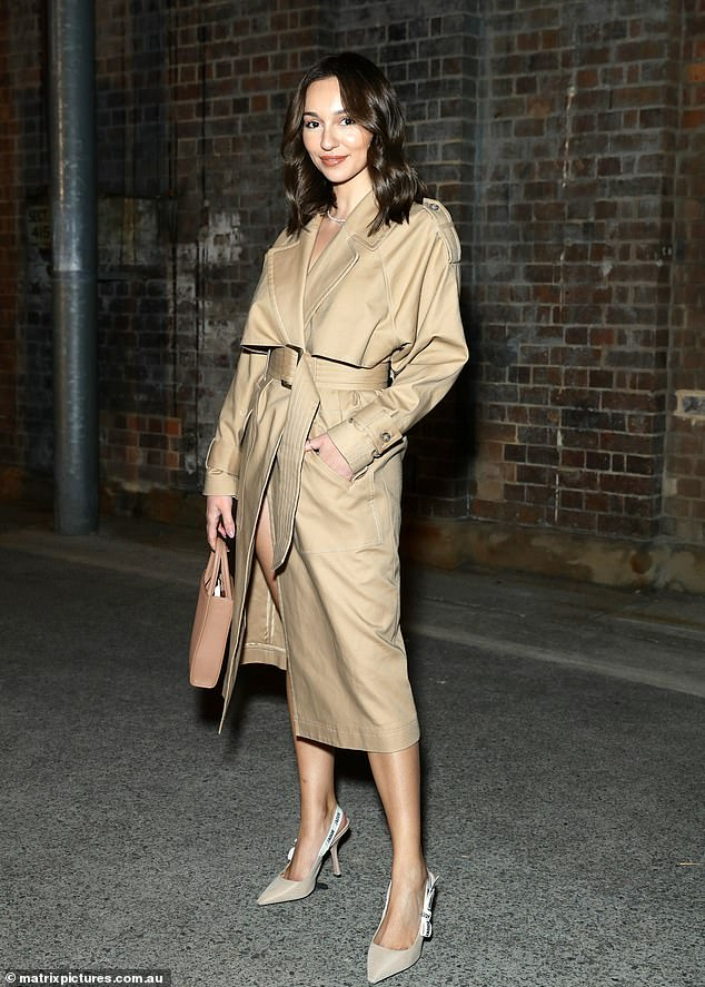 Classic:The Bachelor's Bella Varelis (pictured) opted for classic chic in a beige trench coat, under which she appeared to have on very little