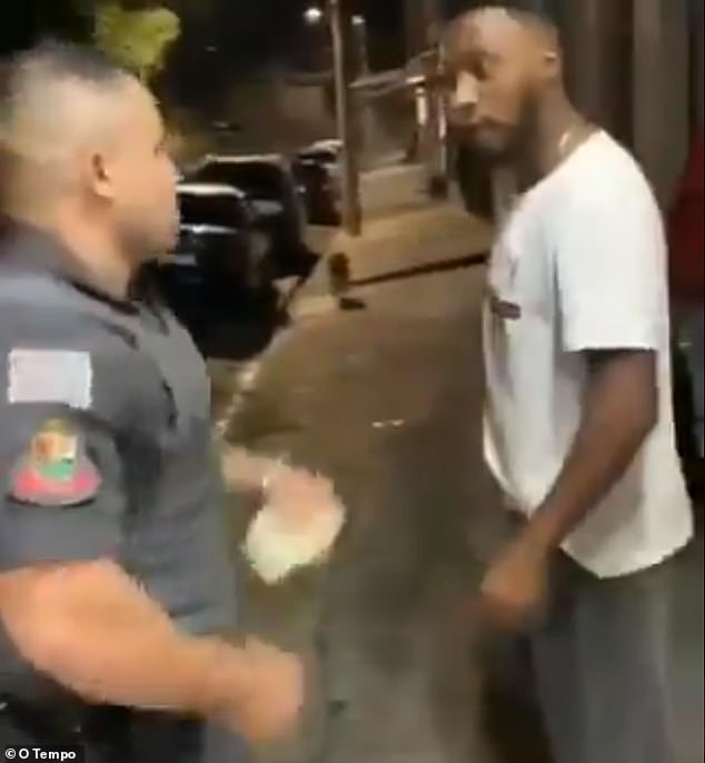 Police officer Oliveira (left) and Kaio Souza (right) stare at each other before the cop delivered a punch to Souza's face during a traffic stop