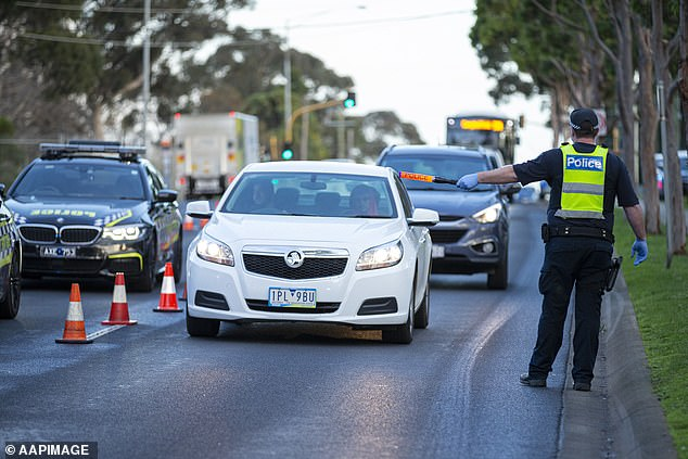 Police officers direct traffic at a roadblock site in Broadmeadows, Melbourne, in July last year